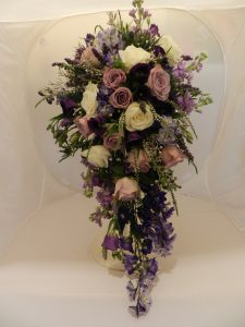 A gorgeous shower bouquet in purple, lilacs and ivory