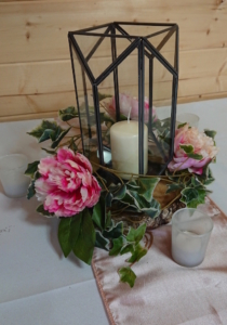 Glass lantern with foliage and blooms